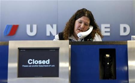 An United Airlines employee works behind a check-in counter at O'Hare International airport in Chicago, June 4, 2008. REUTERS/Jeff Haynes