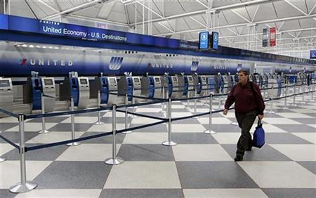 A passenger walks by the empty counter at the United Airlines Terminal at O'Hare International airport in Chicago June 4, 2008. REUTERS/Jeff Haynes