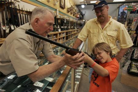 Hunter McConathy (C), 7, holds a hunting rifle with a short stock as his father Bryan (R) and Cabela's salesman Russ Duncan (L) watch him at the Cabela's store in Fort Worth, Texas June 26, 2008. REUTERS/Jessica Rinaldi