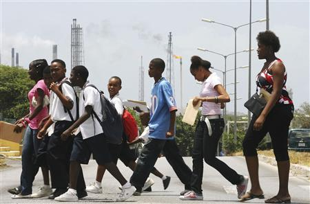 Schoolchildren walk past the Isla refinery in Willemstad on the island of Curacao in this picture taken June 17, 2008. The ageing Isla refinery on this small Caribbean island, operated by Venezuelan state oil company PDVSA, faces growing complaints by residents and several lawsuits charging its industrial emissions cause health problems ranging from chronic coughing to cancer. REUTERS/Jorge Silva