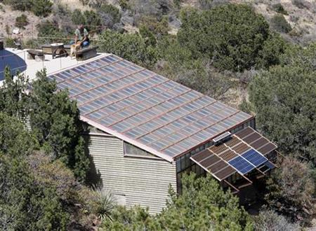 A view of a greenhouse with a solar panel attached for heating water, which architect Todd Bogatay constructed from discarded windows found at the Phelps Dodge copper mine and rebuilt with dual pane glass, near Bisbee, Arizona, May 14, 2008. Leaders in the U.S. solar energy industry blasted the U.S. government on Monday for a freeze on applications for new solar projects on public land in six Western states. REUTERS/Jeff Topping