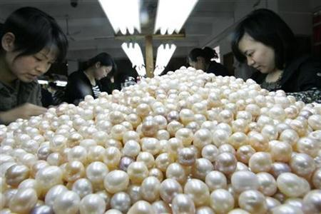 Workers sort artificially cultivated freshwater pearls at a pearl production factory in Zhuji, Zhejiang province April 23, 2008. REUTERS/Aly Song