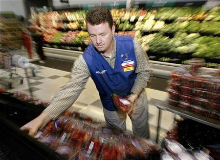 A Wal-Mart associate stocks produce in a file photo. Wal-Mart is sourcing more produce sold in its U.S. supercenters and Neighborhood Market stores from local farmers as it tries to offset the soaring transportation costs that are driving up food prices. REUTERS/Jeff Mitchell
