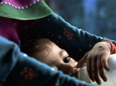 A seven-month-old baby drinks from a bottle inside a hut in Mumbai in a 2007 file photo. REUTERS/Sima Dubey