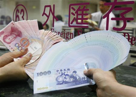 Staff members pose for the media with Chinese yuan notes at the Bank of Taiwan head office in Taipei June 30, 2008. Taiwan allowed its banks to trade in the Chinese yuan (renminbi) currency on Monday, to prepare for the arrival of Chinese tourists on July 4. The Chinese bank notes will also be available at foreign-currency trading counters at tourist hotels, airports and gift stores. REUTERS/Nicky Loh