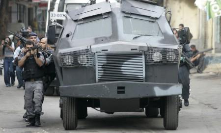 Police raise their weapons near an armoured vehicle during an operation against drug gangs at the Complexo do Alemao slum in Rio de Janeiro in this June 27, 2007 file photo. REUTERS/Bruno Domingos