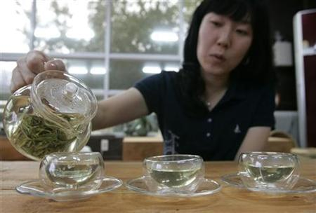 A woman pours hot water to make green tea at a traditional tea house in Boseong, September 23, 2007. A few cups of green tea each day may help prevent heart disease, Greek researchers said on Wednesday. REUTERS/Han Jae-Ho