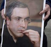 <p>Сторонник экс-главы ЮКОСа Михаила Ходорковского держит его портрет на демонстрации протеста в Москве 31 мая 2008 года. Защита наиболее известного российского узника Михаила Ходорковского, которого Запад считает политзаключенным, надеется на перемену его участи при новом президенте, Дмитрии Медведеве, сказал адвокат Юрий Шмидт (REUTERS/Thomas Peter)</p>
