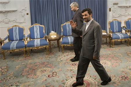 Iran's President Mahmoud Ahmadinejad (R) waves to journalists as Iranian chief nuclear negotiator Saeed Jalili stands in the background before an official meeting in Tehran July 1, 2008. REUTERS/Raheb Homavandi