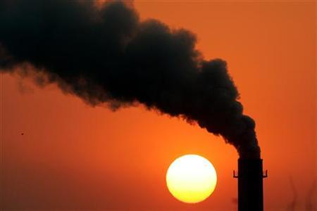 Smoke billows from a power station during sunset in New Delhi, February 16, 2005. REUTERS/Kamal Kishore KK/GB