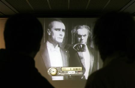 Two men watch a copy of Fritz Lang's film ''Metropolis'' during a news conference where it was presented in Buenos Aires, July 3, 2008. REUTERS/Marcos Brindicci