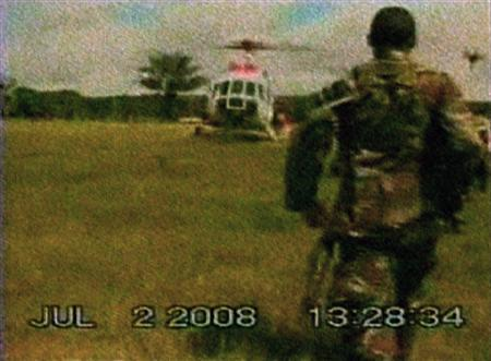 A Revolutionary Armed Forces of Colombia (FARC) guerrilla watches hostages being moved towards a helicopter during a rescue operation in Colombia July 2, 2008 in this frame grab taken on July 4, 2008. REUTERS/Handout