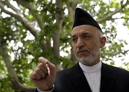 Afghan President Hamid Karzai interacts with the media members after a news conference in Kabul June 15, 2008. Karzai has ordered an investigation into a U.S.-led coalition airstrike that local officials say killed 15 civilians, but the U.S. military says killed only armed Taliban militants. REUTERS/Ahmad Masood