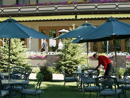A woman prepares tables for lunch at the Sun Valley Resort in Sun Valley, Idaho, July 2007. Major media executives packed their bathing suits, BlackBerrys and iPods this weekend and headed for their version of summer camp -- the annual gathering put together by financier Herb Allen in this exclusive resort. REUTERS/Rick Wilking
