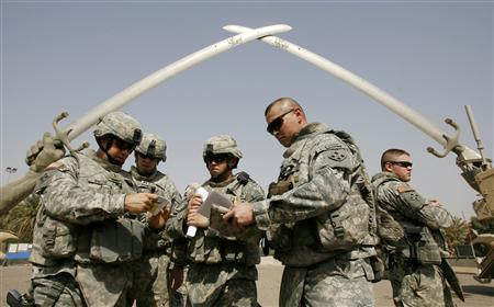 Soldiers discuss their mission under the Cross Sabers monument at the fortified Green Zone in Baghdad July 5, 2008. REUTERS/Erik de Castro