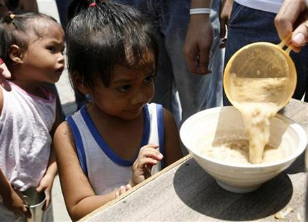 Children queue for free rice porridge distributed by student volunteers as a sign of their protest to the state of hunger and poverty in the country during a feeding program at a slum area in Manila in this recent photo from July 5, 2008. A nutritious diet in early childhood provides a developmental edge that may not be apparent until adulthood, according to a long-term study of Guatemalan villagers released on Monday.REUTERS/Cheryl Ravelo