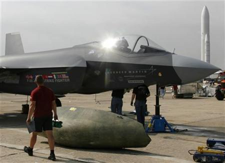Workers prepare a F-35 joint strike fighter four days before the opening of the 47th Paris Air Show at the Le Bourget airport near Paris June 14, 2007. REUTERS/Pascal Rossignol