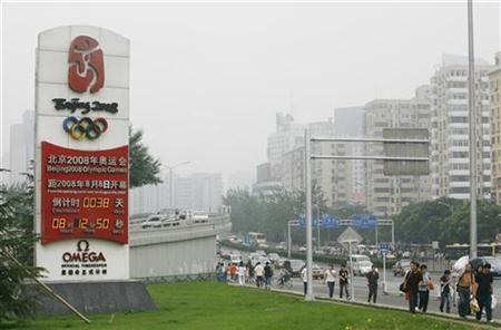 Chinese residents and vehicles pass an Olympic countdown clock that reads 38 days before the 2008 Beijing Olympic Games as China's capital city is shrouded in smog July 1, 2008. REUTERS/Claro Cortes IV