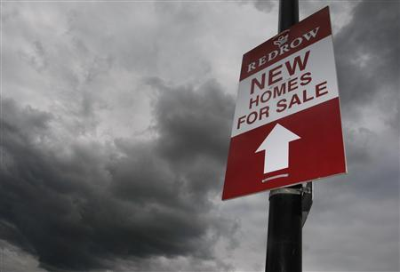 Rain clouds gather behind a sign advertising a new housing development in Manchester, northern England, July 8, 2008. REUTERS/Phil Noble