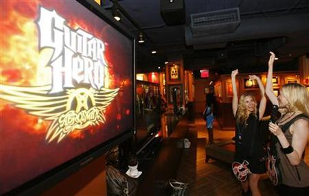 Two women play the new video game ''Guitar Hero: Aerosmith'' before the game release press conference in New York, June 27, 2008. REUTERS/Lucas Jackson