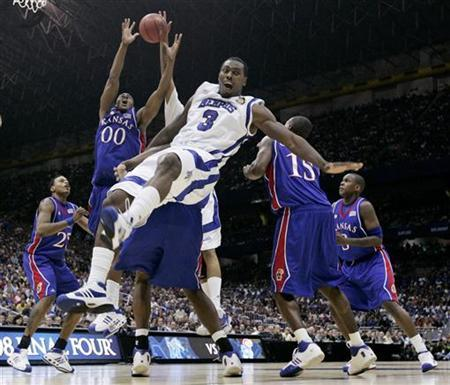 Memphis Tigers' forward Joey Dorsey (3) loses control under the boards as Kansas Jayhawks' Darrell Arthur (00) pulls in a rebound during the first half of their NCAA Men's Final Four championship basketball game in San Antonio, Texas, April 7, 2008. REUTERS/Jeff Haynes