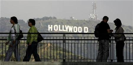 Tourists pause on a walkway at a shopping mall which offers a view of the famed Hollywood sign at the hills in California March 14, 2008. REUTERS/Fred Prouser