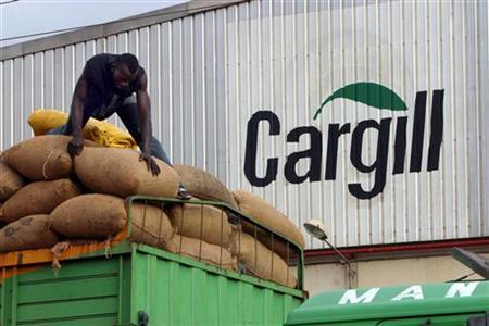 A man gathers bags of cocoa beans at the Cargill factory in San Pedro, the main exporting cocoa port in south western Ivory Coast, October 29, 2004. REUTERS/Luc Gnago