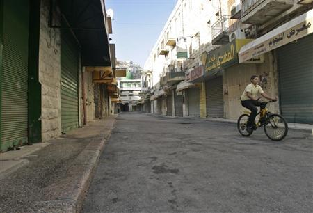 A Palestinian boy rides a bicycle on an empty street in the West Bank city of Nablus July 9, 2008. REUTERS/Abed Omar Qusini