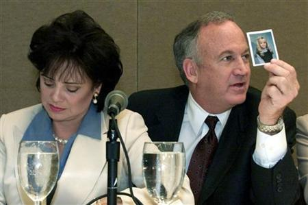 Patsy Ramsey looks down as her husband John (R) produces a picture of JonBenet Ramsey during a press conference in Atlanta, May 5, 2000. REUTERS/Tami Chappell