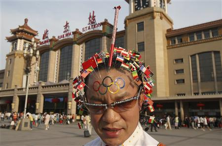 Wei Shengchu, 58, a supporter of traditional Chinese medicine, poses for photos with his head covered with acupuncture needles depicting 205 national flags and an Olympic torch, in front of Beijing Railway Station July 7, 2008. Wei wanted to express his well wishes for the upcoming Beijing Olympic Games as well as to promote traditional Chinese medicine, local media reported. Picture taken July 7, 2008. REUTERS/Henry Lee