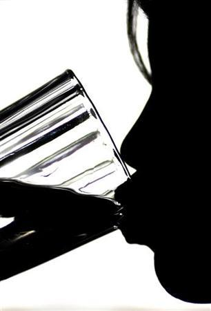 A girl is silhouetted as she drinks a glass of tap water at her home in Loughborough, central England, December 2, 2004. REUTERS/Darren Staples
