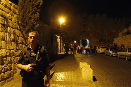 An Israeli policeman stands guard next to the Lions Gate in the Old City of Jerusalem after a shooting attack July 12, 2008. Two Israelis were wounded in a shooting attack late Friday near the Lions Gate in the Old City of Jerusalem, local media reported. REUTERS/Baz Ratner