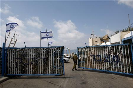 An Israeli soldier opens a gate at the Rosh Hanikra border crossing with Lebanon, in northern Israel, July 15, 2008. REUTERS/Ronen Zvulun