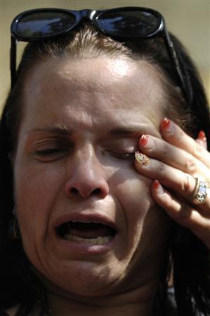 An Israeli woman cries outside the family home of Israeli reserve soldier Eldad Regev in the northern city of Kiryat Motzkin July 16, 2008. REUTERS/Amir Cohen