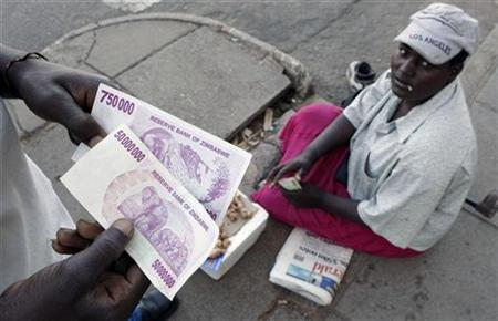 A Zimbabwean holds a newly issued fifty million dollar note at a street traders stand in the capital Harare, April 4, 2008. REUTERS/Mike Hutchings