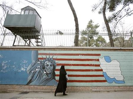 An Iranian woman walks past a mural on the wall of the former U.S. embassy in Tehran February 21, 2007. REUTERS/Morteza Nikoubazl