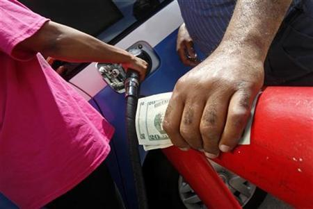 A gas station owner holds on to the money given to him by a customer to prepay for fuel at his station in Arlington, Virginia, June 11, 2008. REUTERS/Jim Young