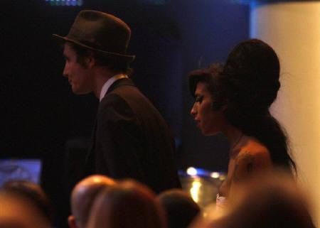 Amy Winehouse (R) leaves the stage with her husband Blake Fielder-Civil during the 2007 Mercury Music Awards at the Grosvenor House hotel in London September 4, 2007.    REUTERS/Kieran Doherty/Files