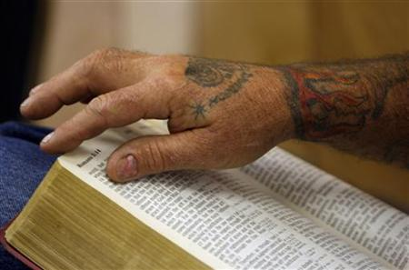 A truck driver turns the pages of his bible at a truck stop in San Antonio, Texas May 11, 2008. REUTERS/Jessica Rinaldi