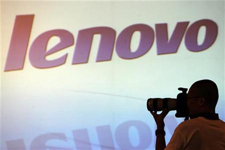 A photographer takes photos in front of a screen during a Lenovo Group Ltd. news conference in Hong Kong May 23, 2007. REUTERS/Paul Yeung