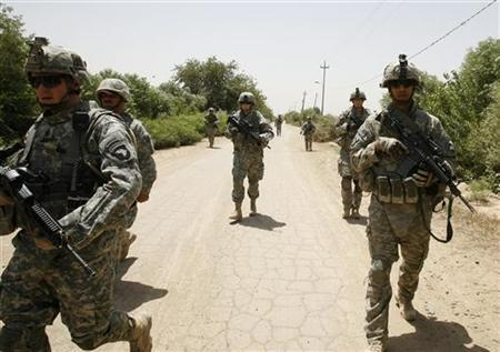 U.S. soldiers from 1-87 Infantry Regiment, 3rd Brigade walk towards a village, to secure the opening of a new community centre in Sayafiyah southeast of Baghdad May 20, 2008. REUTERS/Erik de Castro