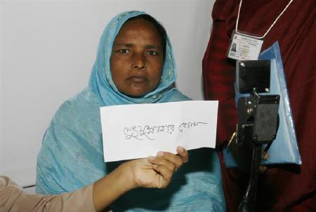 A woman has her photo taken with her name held up in front of her in Sreepur, 70 km from the Bangladeshi capital Dhaka, June 10, 2007. REUTERS/Rafiqur Rahman/Files