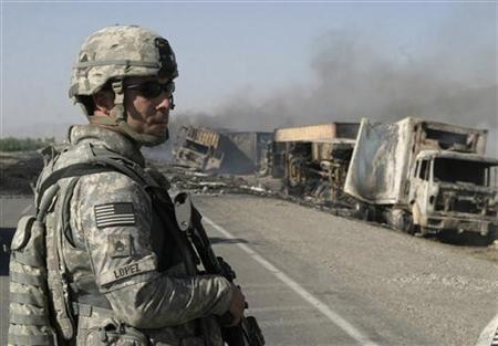 A U.S. soldier keeps watch at the site where Taliban militants set fire to a convoy of supply trucks in Ghazni, southeast of Afghanistan June 24, 2008. REUTERS/Shir Ahmad