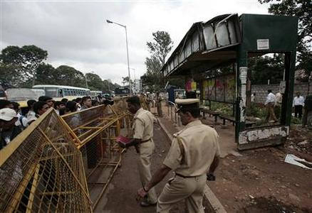 Policemen stand guard at the Madivala bus stand where a woman reportedly died in a bomb blast in Bangalore July 25, 2008. REUTERS/Stringer