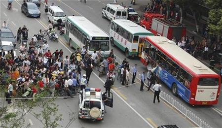 Police inspect the scene of a bus explosion in Kunming, Yunnan province July 21, 2008. REUTERS/China Daily