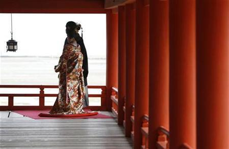 A bride in traditional Japanese wedding attire poses for photos with her groom at the Itsukushima Shrine in Hatsukaichi, southwestern Japan April 16, 2008. REUTERS/Toru Hanai