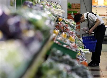 A customer looks at fruit and vegetables on sale at a supermarket in central Beijing June 20, 2008. REUTERS/David Gray