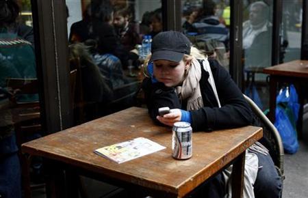 A woman uses her mobile phone as she sits outside a restaurant at Brick Lane Sunday Market in east London March 2, 2008. REUTERS/Alessia Pierdomenico