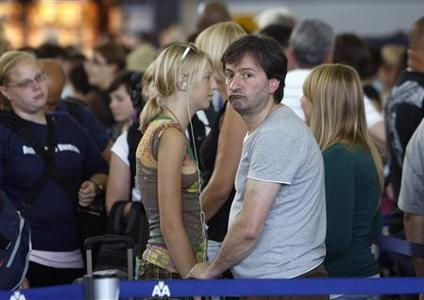 Customers wait in line after a computer glitch crippled the baggage handling system at the American Airlines' Terminal 8 at New York's John F. Kennedy International Airport July 30, 2008. REUTERS/Joshua Lott
