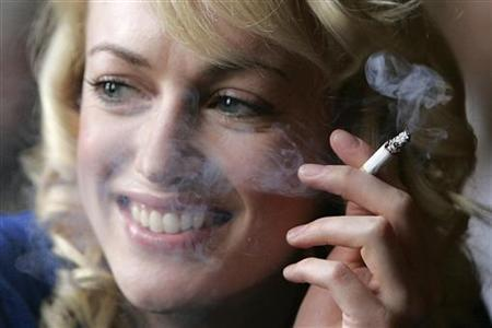 A woman smokes a cigarette in a bar in Glasgow, March 23, 2006. REUTERS/Tony Marsh